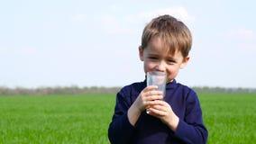 Het gelukkige kind drinkt vruchtensap van een glas in aard Gezonde en juiste voeding van kinderen ecologisch stock videobeelden