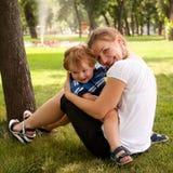 Het gelukkige kind en vrouwen openlucht spelen Stock Foto's