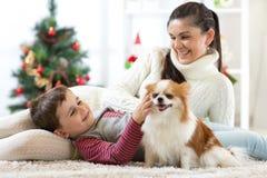 Het gelukkige kind en zijn mamma liggen op vloer dichtbij Kerstboom en omhelzen hond Zij bekijken huisdier en het glimlachen stock foto