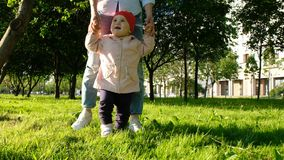Het gelukkige kind leert om in het park bij zonsondergang te lopen De moeder helpt de baby om de eerste maatregelen te treffen royalty-vrije stock foto's