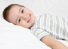 Het gelukkige kind ligt op wit bed Stock Foto