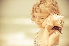 Het gelukkige kind luistert aan zeeschelp bij het strand Stock Foto's