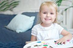 Het gelukkige kind schilderen met gouache en waterverfverven op de schildersezel binnen stock afbeelding