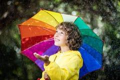 Het gelukkige kind spelen in de regen stock foto's