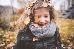 Het gelukkige kind spelen met bladeren in de herfst Seizoengebonden openluchtactiviteiten met jonge geitjes Stock Afbeeldingen