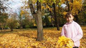 Het gelukkige kind spelen met de herfstbladeren stock video