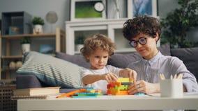 Het gelukkige kind spelen met houten blokken die met mamma bouwen concentreerde zich thuis op spel stock videobeelden