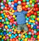 Het gelukkige kind spelen met kleurrijke plastic ballen Stock Afbeelding