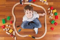Het gelukkige kind spelen met speelgoed Jongenszitting op houten vloermier die omhoog camera en het glimlachen bekijken stock afbeelding
