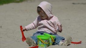 Het gelukkige kind spelen met zand bij het strand in de zomer stock video