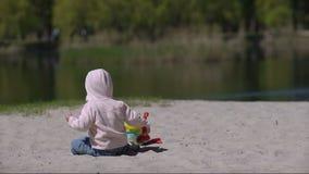 Het gelukkige kind spelen met zand bij het strand in de zomer stock footage