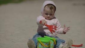 Het gelukkige kind spelen met zand bij het strand in de zomer stock videobeelden