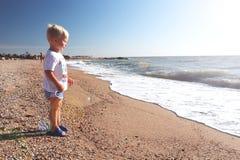 Het gelukkige kind spelen op het strand stock fotografie