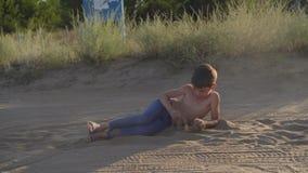 Het gelukkige kind springt op alle fours en ligt in steppestof en zand, vrij spel stock videobeelden