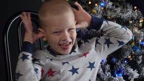Het gelukkige kind toont grimassen voor Kerstboom in slingers en groene UFOballen van brand, gloeiende gebieden, die lichten opvl stock video