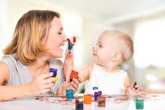 Het gelukkige kind trekt op het gezicht van zijn moeder. Stock Foto's