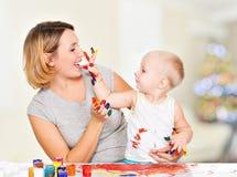 Het gelukkige kind trekt op het gezicht van zijn moeder. Stock Afbeelding