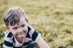Het gelukkige kind, weinig jongen kijkt neer, peinzende blik en holding in handen de groei in openlucht Ruimte voor tekst Gestemd stock foto's
