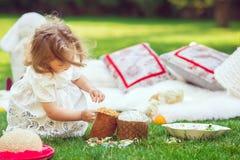Het gelukkige kind zit op een weide die met Pasen-decoratie plaing royalty-vrije stock afbeeldingen