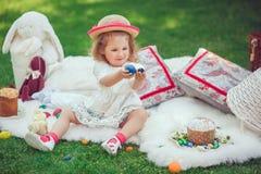 Het gelukkige kind zit op een weide die met Pasen-decoratie plaing stock afbeeldingen