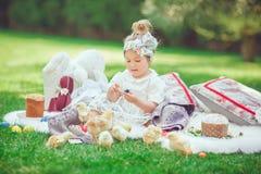 Het gelukkige kind zit op een weide kijkt aan Pasen-decoratie stock afbeelding