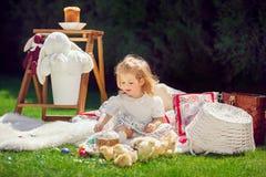 Het gelukkige kind zit op een weide rond Pasen-decoratie stock afbeelding