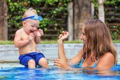 Het gelukkige kind zwemt met mooie moeder in pool Stock Afbeeldingen