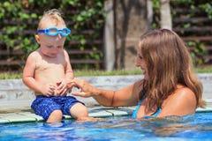 Het gelukkige kind zwemt met mooie vrouw in pool Royalty-vrije Stock Foto's