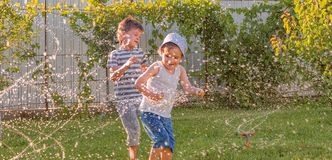 Het gelukkige kinderen openlucht spelen Blije siblings die pret op zonnige de zomerdag hebben Het gelukkige kinderen openlucht sp stock afbeeldingen