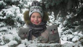 Het gelukkige kindmeisje bevindt zich onder de spar en speelt met met de hand gemaakte vuisthandschoenen met katjes, de winter bo stock video