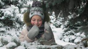 Het gelukkige kindmeisje bevindt zich onder de spar en speelt met met de hand gemaakte vuisthandschoenen met katjes, de winter bo stock videobeelden