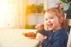 Het gelukkige kindmeisje eet aardbeien in de keuken van het de zomerhuis Stock Foto