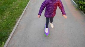 Het gelukkige kindmeisje in jasje rolt op purper skateboard op straat in park stock footage