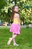 Het gelukkige kindmeisje kleedde zich in het toevallige doek stellen, kinderjarenconcept, zomer in stadspark Royalty-vrije Stock Afbeelding