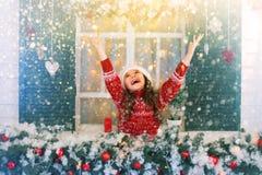 Het gelukkige kindmeisje rekt haar hand uit om dalende sneeuwvlokken te vangen stock foto's