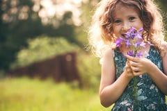 Het gelukkige kindmeisje spelen met boeket van klokjes in de zomer Royalty-vrije Stock Afbeelding