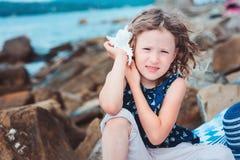Het gelukkige kindmeisje in streephoed het spelen op het strand en luistert aan overzeese shell stock afbeeldingen