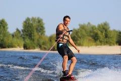 Het gelukkige knappe mens wakesurfing royalty-vrije stock afbeeldingen