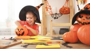 Het gelukkige lachende kindmeisje in een heksenhoed eet snoepjes in Hallow Stock Foto