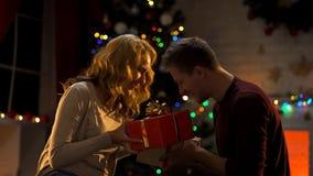 Het gelukkige lachende paar die elkaar Kerstmis geven stelt gelijktijdig voor stock fotografie