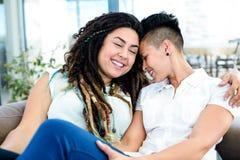Het gelukkige lesbische paar ontspannen op bank Stock Foto