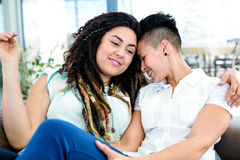 Het gelukkige lesbische paar ontspannen op bank Royalty-vrije Stock Afbeeldingen