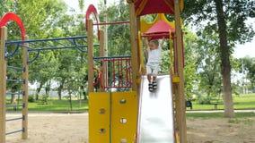 Het gelukkige leuke baby spelen in een park van kinderen in openlucht De jongen rolt een heuvel naar beneden Beweging, rust en ou stock videobeelden