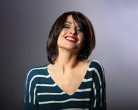 Het gelukkige luid lachen met brede glimlach jonge vrouw met korte hai stock afbeelding