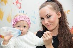 Het gelukkige mamma en babymeisje drinken van fles Het concept kinderjaren en familie Stock Foto's