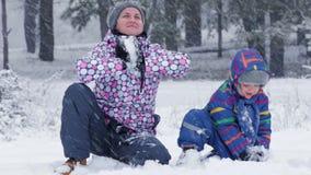 Het gelukkige mamma en de baby spelen in een sneeuwpark, werpend sneeuw in de camera Afzonderlijk, familieverhoudingen, openlucht stock footage