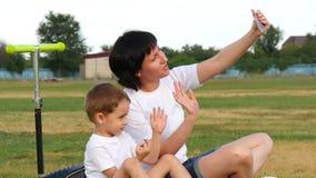 Het gelukkige mamma en de baby zitten op het groene gras in het park en nemen een selfie met hun telefoon stock footage