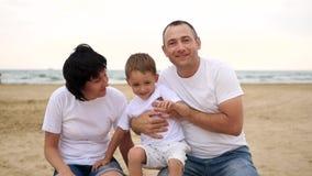 Het gelukkige mamma en de papa kussen hun kind die op een zandig strand tegen het overzees, in langzame motie glimlachen stock videobeelden