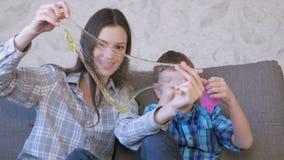 Het gelukkige mamma en de zoon spelen met slijmzitting op de bank Het uitrekken van slijm die door het slijm kijken stock videobeelden