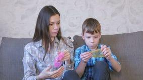 Het gelukkige mamma en de zoon spelen met slijmzitting op de bank Het uitrekken van slijm die door het slijm kijken stock footage